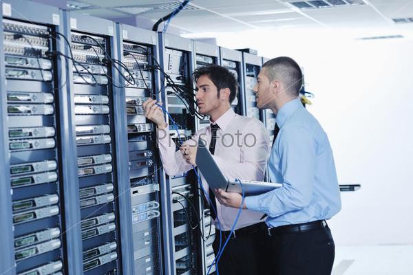 Два инженера в серверной комнате пытаются наладить работу системы