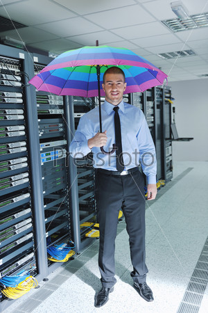 Инженер в серверной комнате с ярким зонтиком в руке. Концепция антивирусной защиты