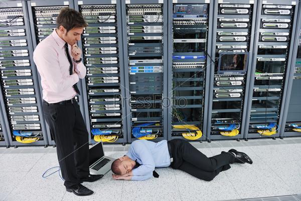 Два уставших инженера в серверной комнате с ноутбуком, не нашедших неполадки