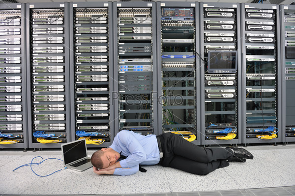 Спящий инженер в серверной комнате с ноутбуком, не нашедший неполадки