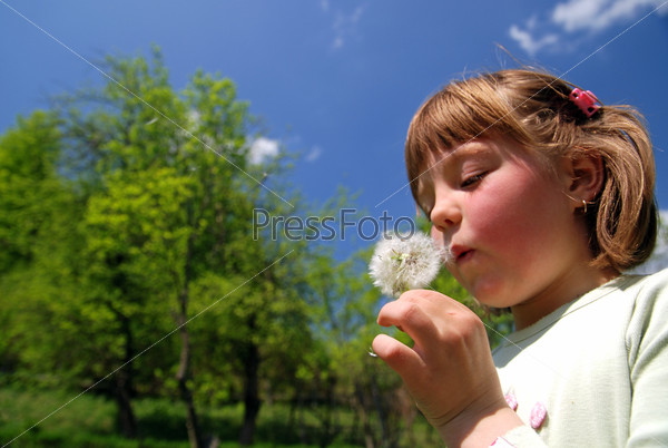 cute girl blowing dundelion