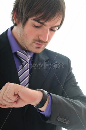 Молодой деловой мужчина в костюме и галстуке смотрит на часы, изолирован на белом фоне