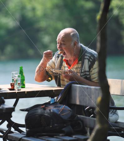 senior man eat desser at outdoor restaurant