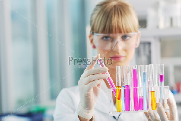 female researcher holding up a test tube in lab