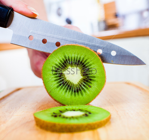Woman's hands cutting kiwi