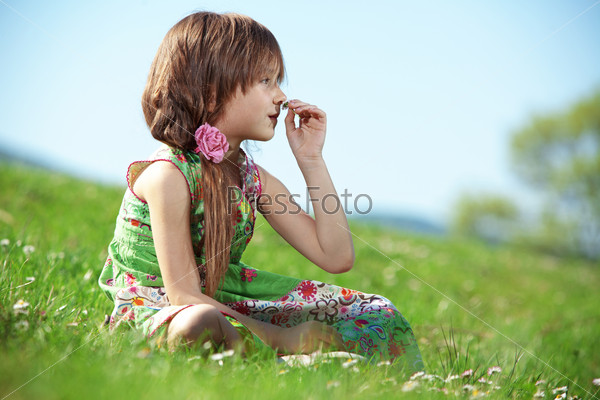 Little girl at green field