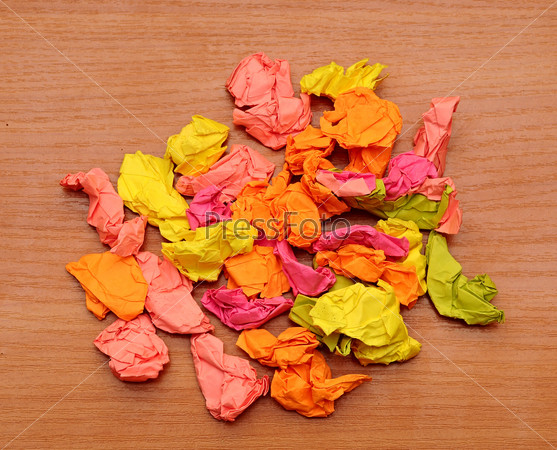 collection of colorful crumpled papers  on a wooden background