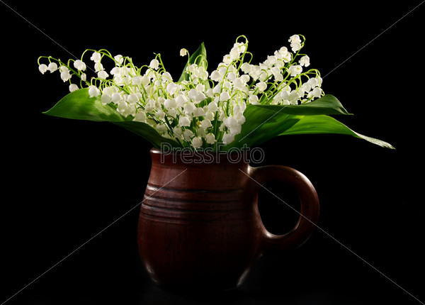 Bouquet lilies of the valley in a ceramic mug.