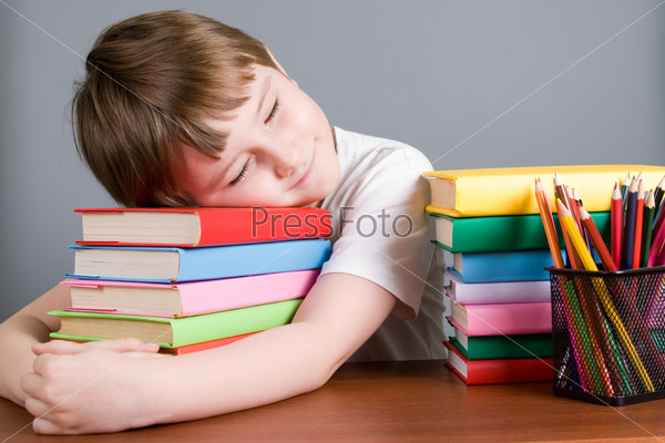 Tired boy sleeps on the books