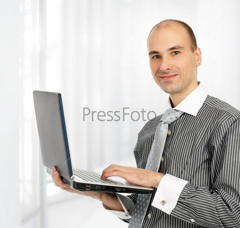 Portrait of a confident young business man with laptop