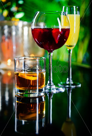 Three different beverages, glass of whiskey, glass of red wine a