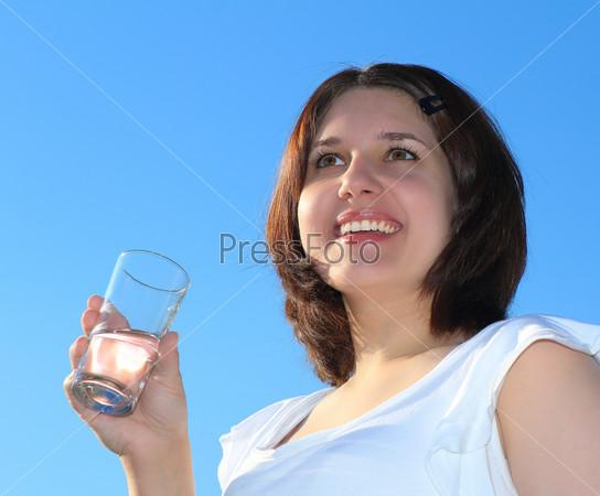 Молодая женщина пьет воду на фоне голубого неба
