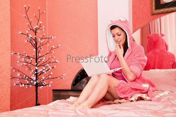 Красивая девушка с ноутбуком на кровати