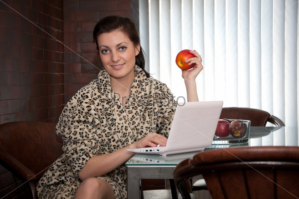Милая девушка с ноутбуком и яблоком