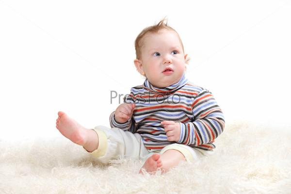 child sitting on a fluffy white skin