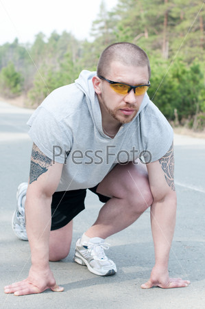 Молодой бегун на низком старте на открытом воздухе