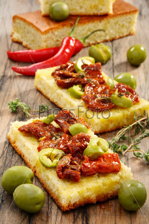 Appetizer of sun-dried tomatoes, olives and thyme.