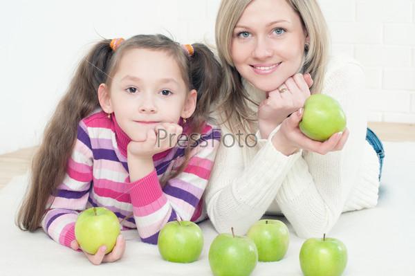 Молодая мама с дочерью, лежа на полу с зелеными яблоками
