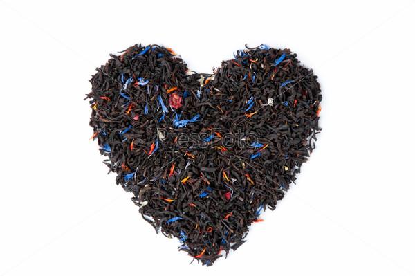 Сердце, выложенное из сухого черного чая на белом фоне