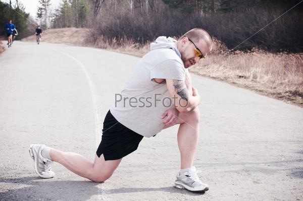 Портрет молодого бегуна, разминающегося на свежем воздухе