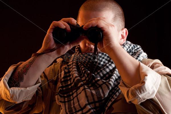Военный в камуфляже с биноклем в руках