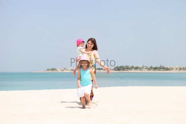 Mother and her two little daughters on the beach