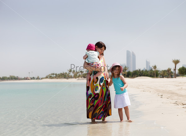 Mother and her little daughters on the beach