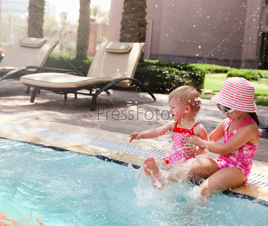 Two little sisters playing in swimming pool
