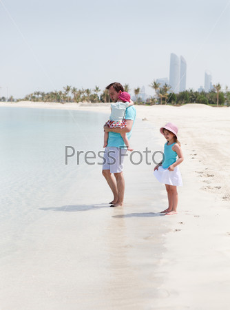 Father and his two little daughters on the beach