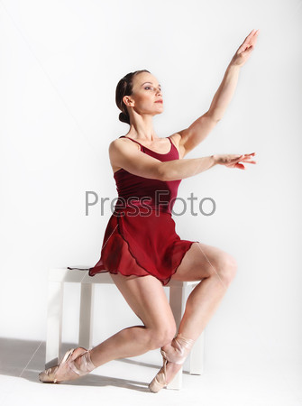 Ballet dancer posing on studio background