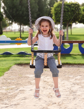 Laughing child on swing in summer park