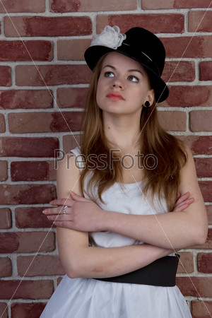 Fashionable young woman posing of a brick wall.