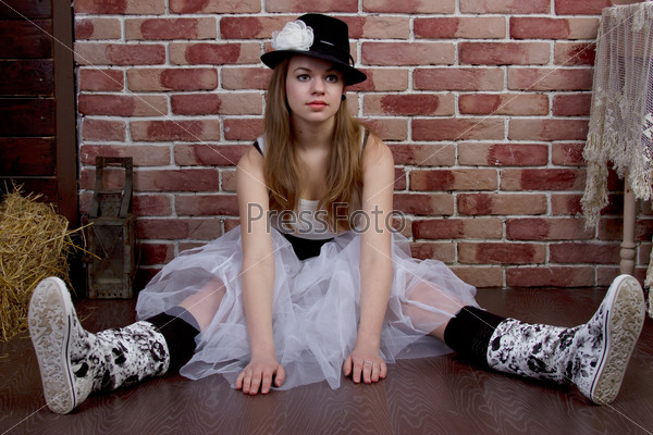Fashionable young woman posing of a brick wall.
