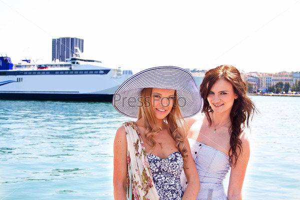 Портрет двух молодых и красивых женщин на фоне большого океанского лайнера