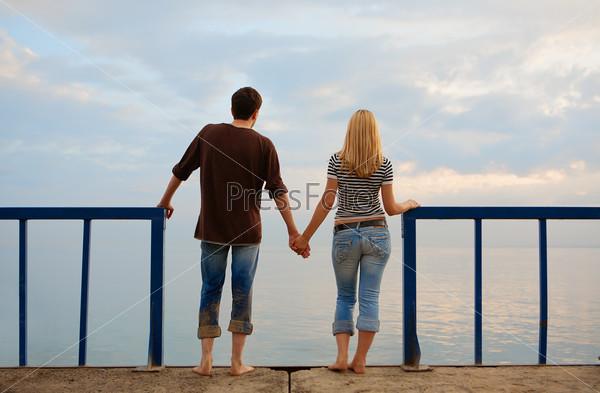 Мужчина и женщина смотрят на море, взявшись за руки