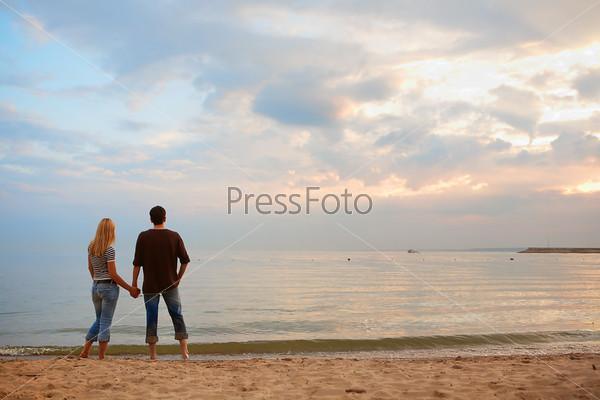 Влюбленная пара на берегу моря любуется закатом