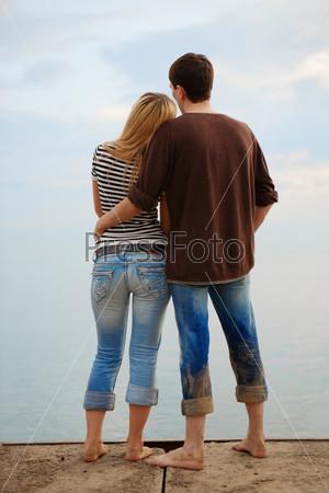 Мужчина и женщина, обнявшись, смотрят на море