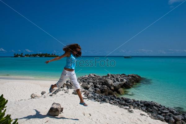 Девушка прыгает  на побережье Индийского океана