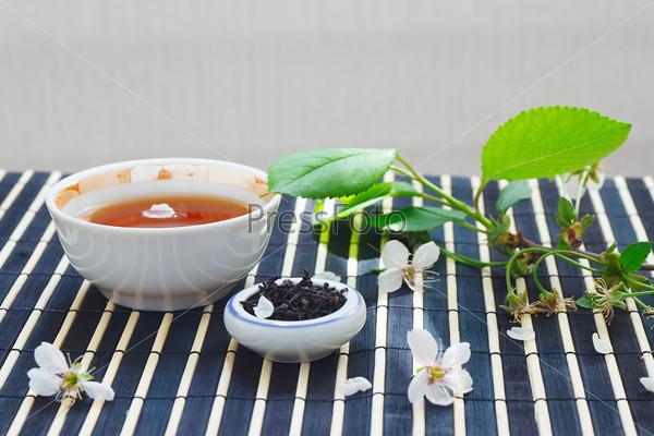 Чашка чая, чайные листья и вишневые цветы на бамбуковой салфетке