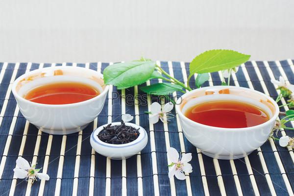 Две чашки чая, чайные листья и вишневые цветы на бамбуковой салфетке