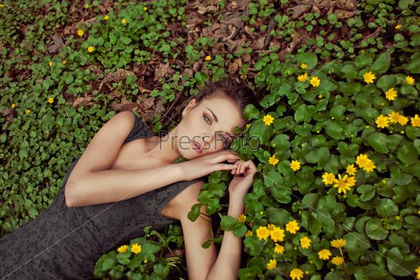 Красивая девушка лежит на поляне в желтых цветах