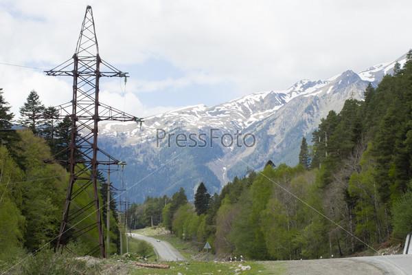 Высоковольтная опора воздушной линии электропередачи на фоне горной местности