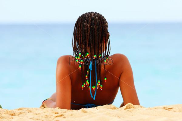 Девушка на пляже с косичками раста