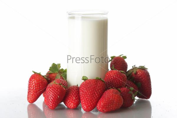 Клубника и стакан молока на белом фоне