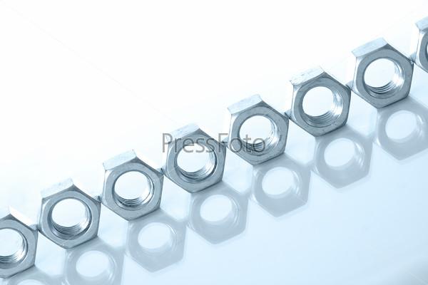 Металлические гайки на белом фоне
