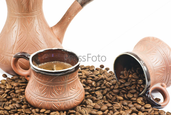 two brown ceramic coffee cup filled  and ceramic coffee maker w