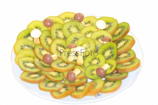 Нарезанные плоды киви и грибочки на тарелке