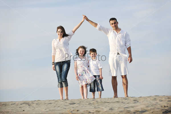 family on beach showing home sign