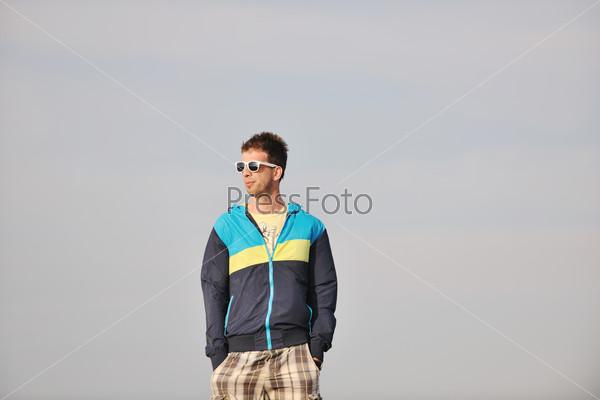 Молодой человек отдыхает на пляже на закате