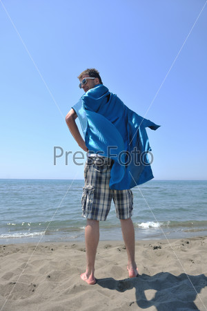 funny superhero standing on beach